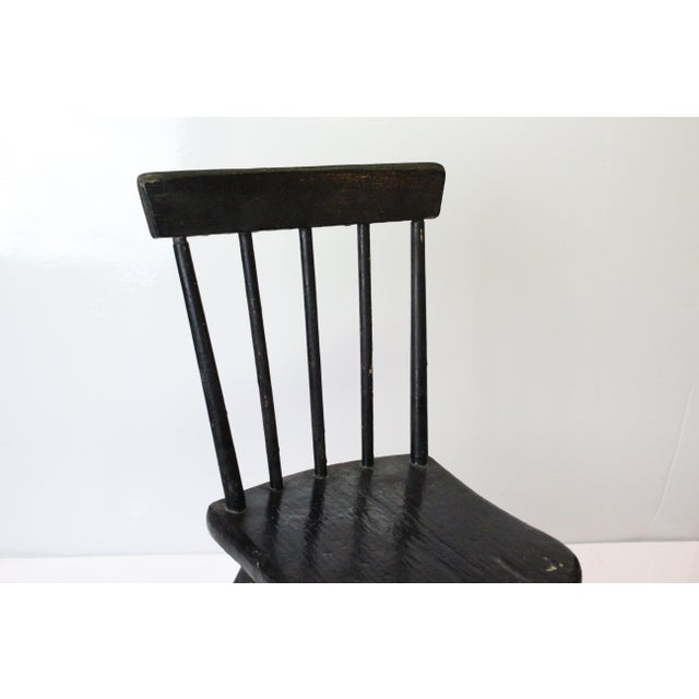 Painted black pine wood fashioned into a miniature Windsor chair for a child.