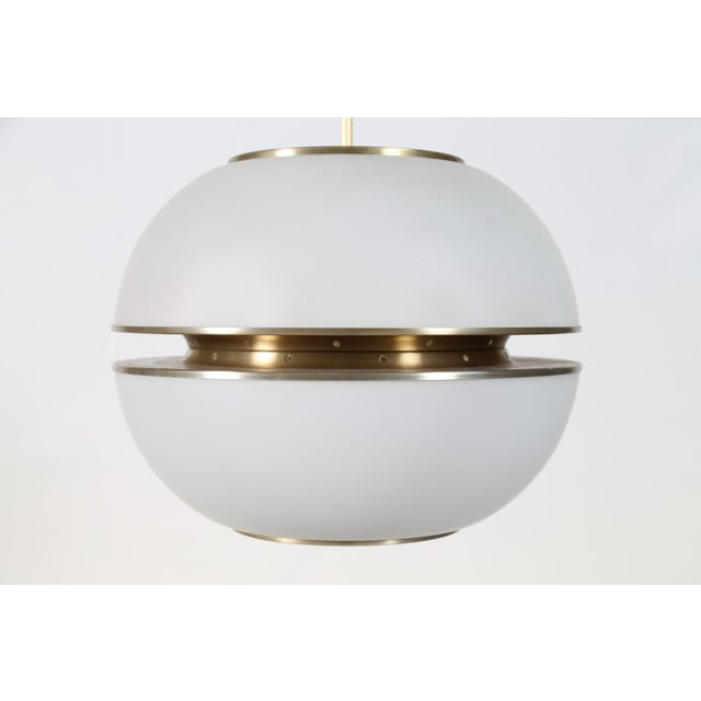 Large, sleek, modernist Lumi chandelier attributed to Oscar Torlasco, in spherical opaline glass bisected by satin finish...