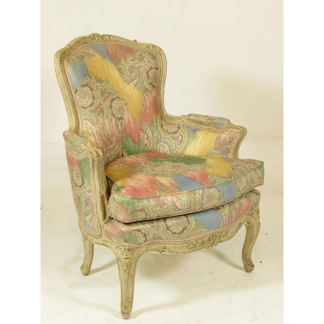 A European imported Louis XV Style hand carved bergere with new Scalamandre silk-blend fabric, down cushion, and a glazed...