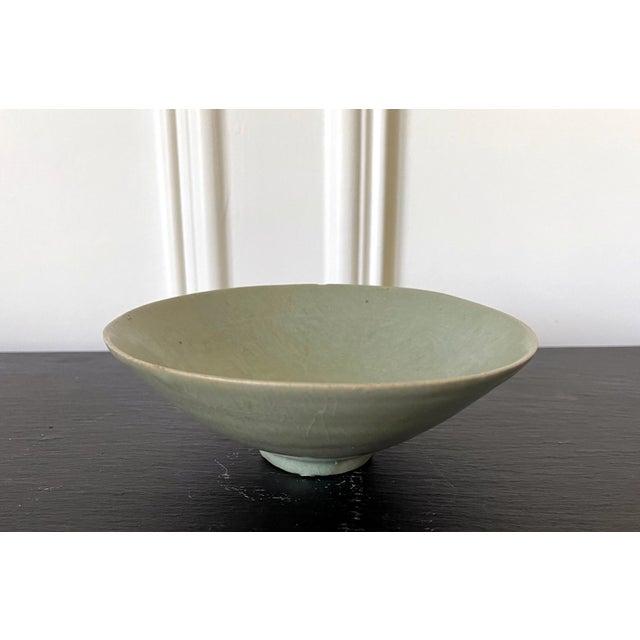 An antique Korean ceramic tea bowl with celadon glaze from Goryeo dynasty, circa 12th century. The thin-walled stoneware...