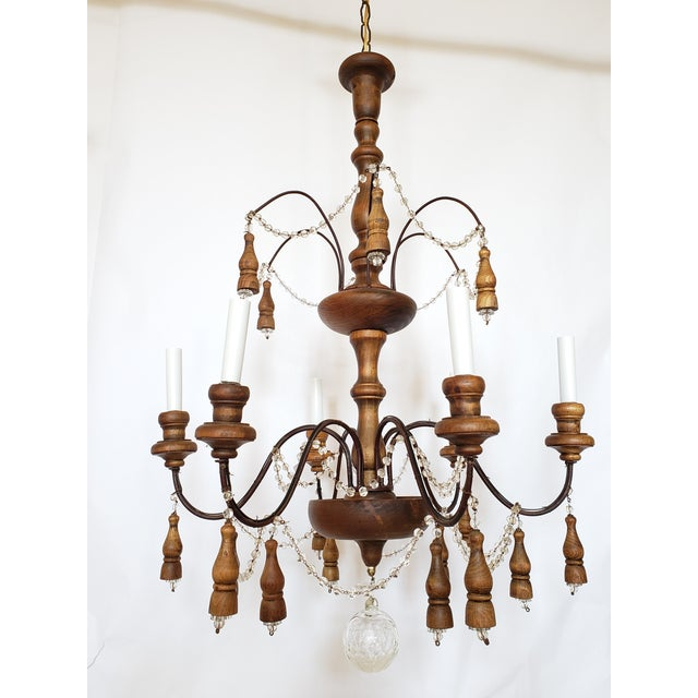 Antique French chandelier made with a wood frame and wrought iron arms. The crystal streamers, wooden tassels bring...