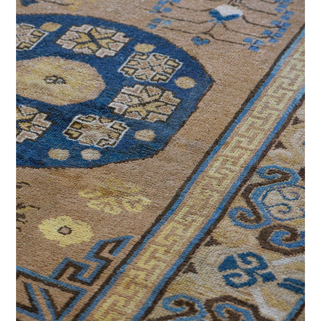 This traditional antique Persian Khotan runner has a sandy-brown field with various delicate floral sprays and hooked...