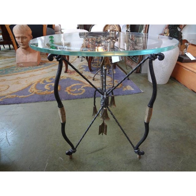 Lovely Italian wrought iron and brass table, side table, drink table or gueridon with arrow and tassel detail. After...