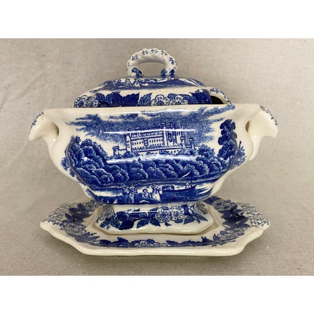 Vintage blue and white ceramic gravy boat with plate. Floral border with scenes of a picnic in front of a castle. A great...