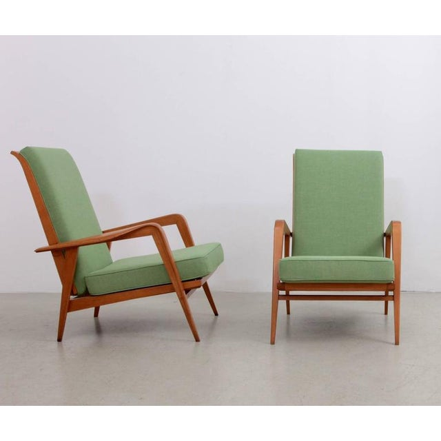 Pair of upholstered armchairs with solid beechwood frame by Etienne Henri Martin. These chairs have two different positions.