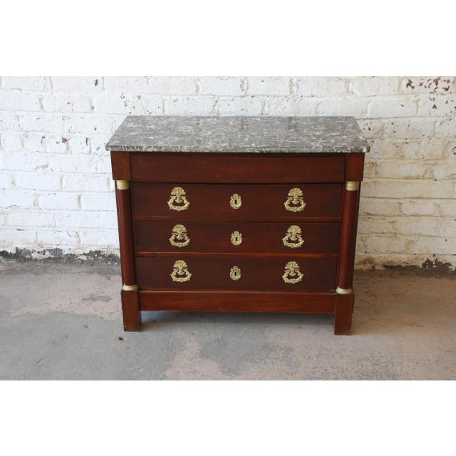 Offering a beautiful mahogany French Empire commode chest of drawers from the 1850s. The four drawer chest has unique...