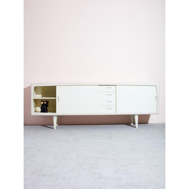 Beautiful well-crafted vintage white danish credenza. Features four slim drawers down the middle and two sliding doors...