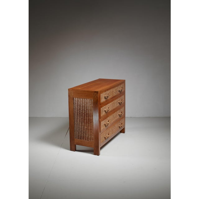 A commode with four drawers by Jean Touret for Marolles. The commode is made of oak with woven wicker on the sides of the...
