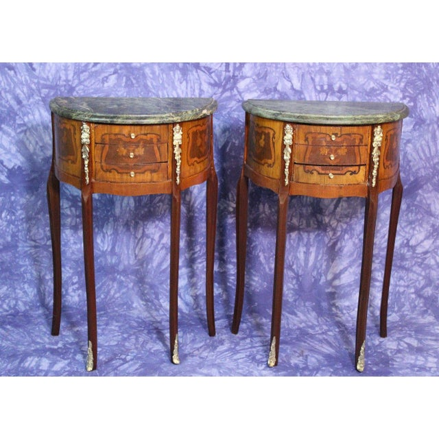 On offer on this occasion is a pair of outstanding French Louis XV style marquetry demi-lune 3-drawer end tables with gilt...