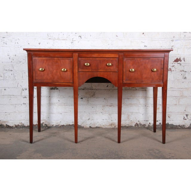 A gorgeous regency style sideboard or credenza By Hekman Furniture USA, Circa 1970s Cherry + yewood + brass hardware...