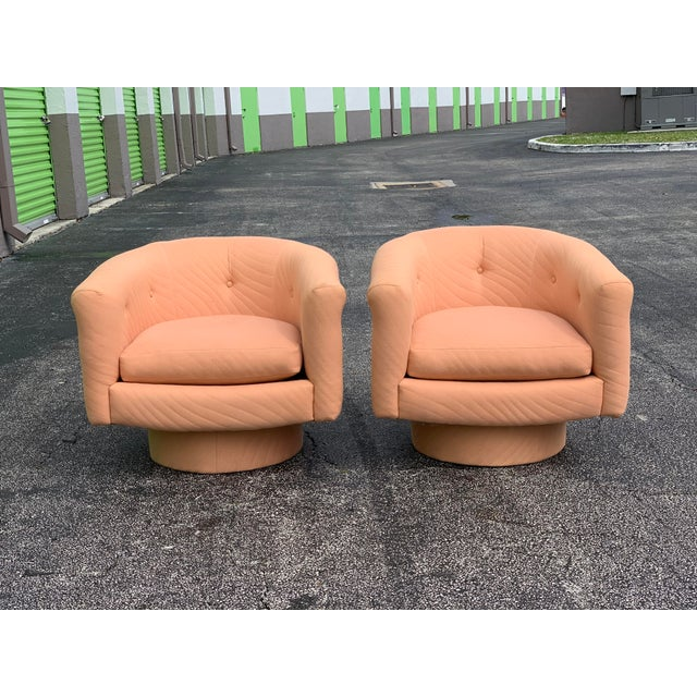 A beautiful pair of 1970s vintage mid century modern swivel tufted lounge chairs in the style of Milo Baughman. Oversized...