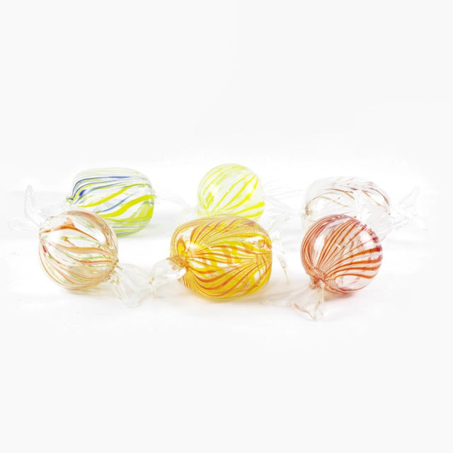 A set of six large Murano style glass candy paperweights, three round and three square. The round glass candies include...