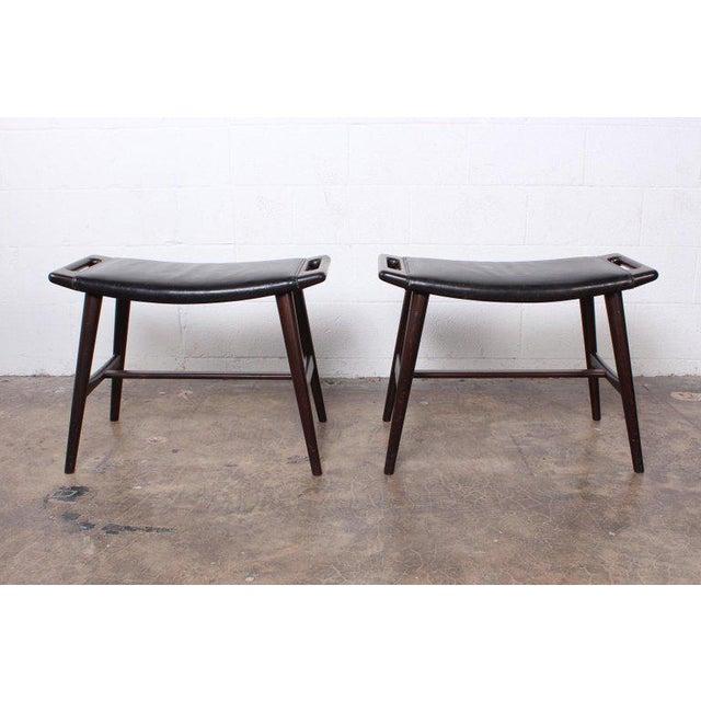 A pair of Hans Wegner AP-30 piano stools in original leather.