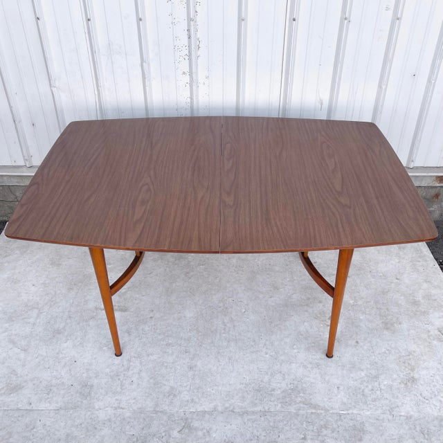 This mid-century dining table opens from 57 inches wide to 80.5 inches wide with two removable table leaves. The sturdy...