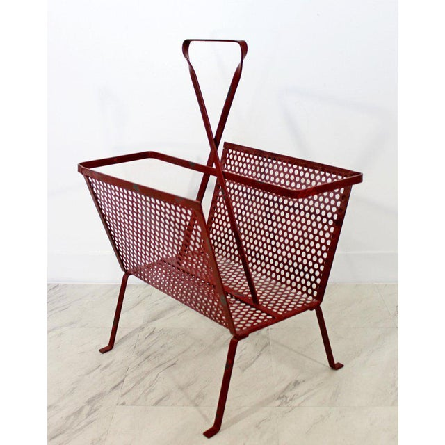 """For your consideration is a small, red painted mesh metal magazine rack. In vintage condition. The dimensions are 15"""" W x..."""
