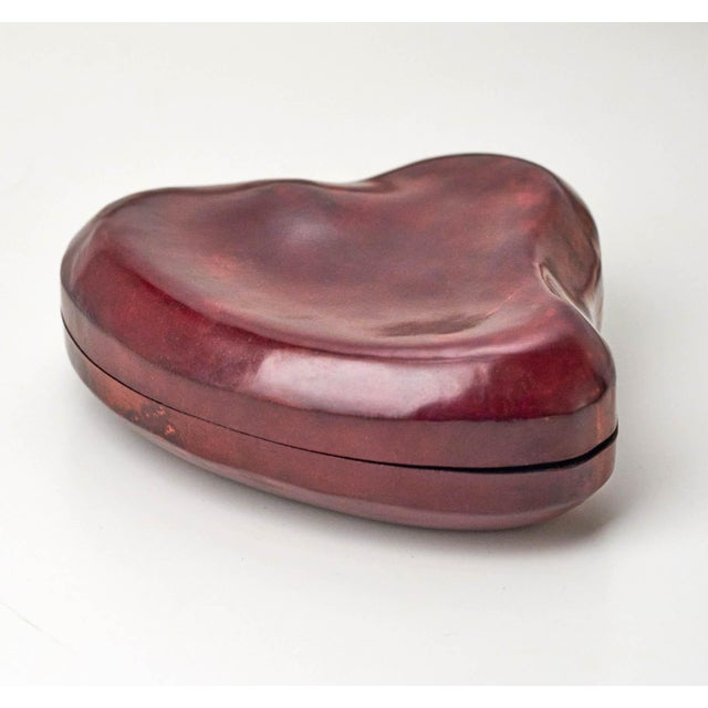 This heart shaped leather box is sold by Tiffany & Co. and was designed by Elsa Peretti. It's brown leather with a black...
