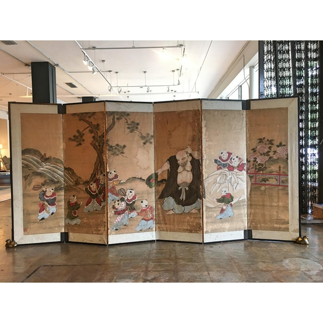 A delightful Japanese six panel painted paper screen, featuring the beloved figure Hotei, Edo Period, early 19th century....