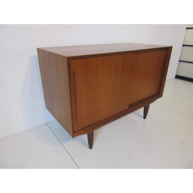 A smaller scaled Danish teak wood two sliding door credenza with open box storage that can be used as a media cabinet ....