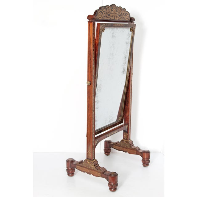 English Regency rosewood cheval mirror elaborately decorated with brass inlay.