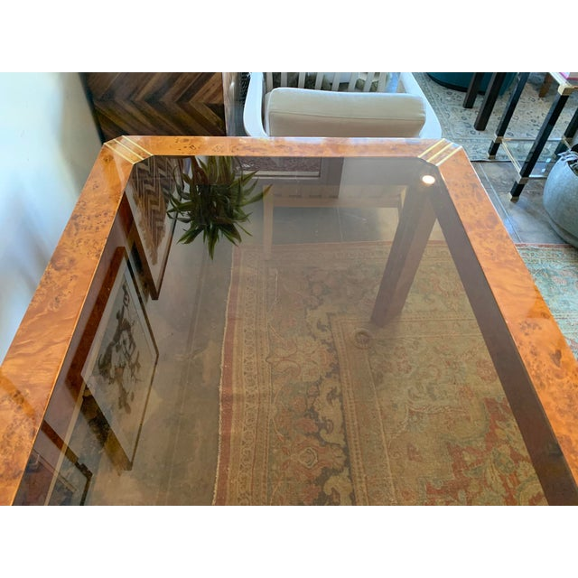 Vintage dining table constructed of burlwood, amber tinted glass and brass detailing. Classic 1970s, fashioned after Milo...