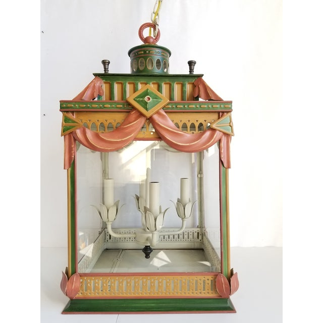 This is a highly decorative tole painted large lantern over-all with colors of rich rusts,green and gold centered with...