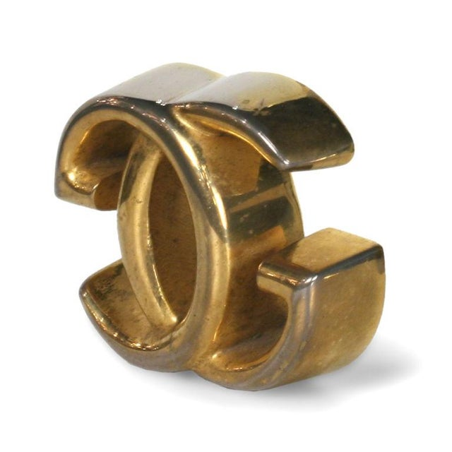 A chic desk accessory paperweight with interlocking 'G's' in brass. Weighs close to one pound. Marked. By Gucci. Italian,...