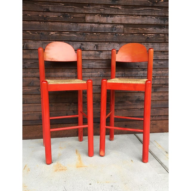 """Fabulous pair of stained red bar stools in the style of Vico Magistretti for Cassina. Marked """"Made in Italy"""" on the bottom..."""
