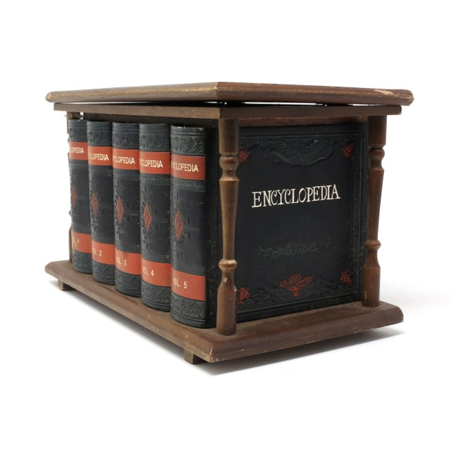 A vintage, carved wood box in the form of a set of leather-bound encyclopedias and stand, disguising a glass liquor bottle...