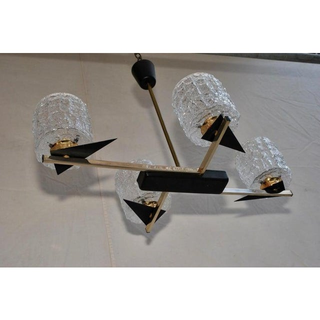 This is a Mid-Century Chandelier with black sharp pointed triangle details and a gold tone brass body. The Shades are...