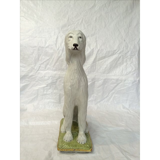 An almost life-sized Italian ceramic Afghan hound sitting upon a cushion statue. Glazed and hand painted. Minor wear...