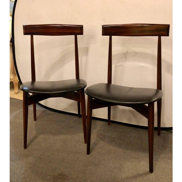 Set of four Mid-Century Modern slat back black leather side chairs. Each in a rosewood finish with new seat cushions.