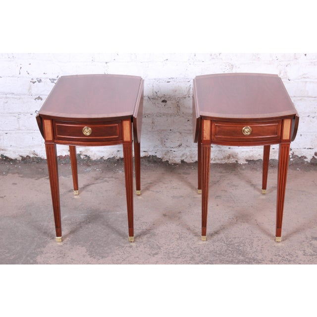 An exceptional pair of Georgian style banded mahogany drop-leaf pembroke side tables by Baker Furniture. The tables...