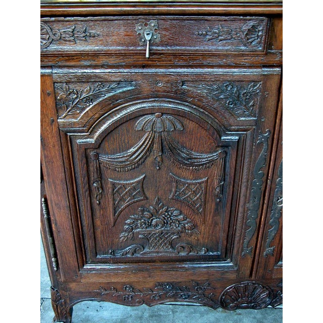 A richly-patinated and well-carved French provincial oak 2-door buffet; the rectangular top with diamond inlay above a...