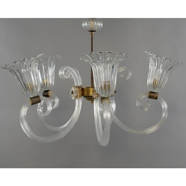 Five-light Barovier clear glass chandelier, circa 1940s. Blown glass ceiling canopy, brass support rod with blown glass...