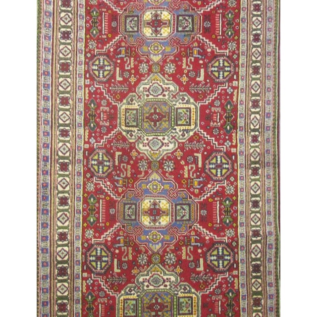 This beautiful rug is hand made, made in Iran. It features a pattern in a vibrant combination of red, green, blue. With...
