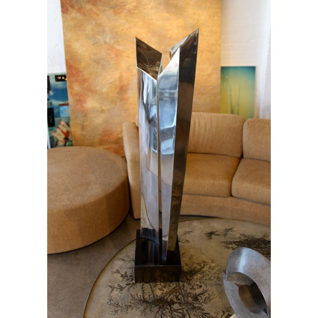 A really spectacular towering steel sculpture on a re-touched and re-painted black wood base. The sculpture is signed on...