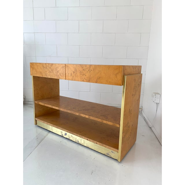 Burlwood and patinated brass bar. The item displays well and sits on small casters. Item shows wood grain throughout, has...