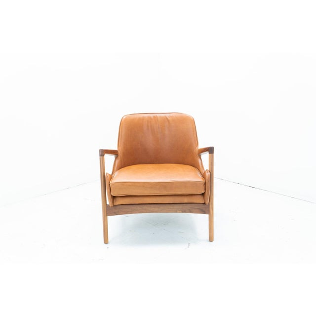 A sleek sculptural Larsen seal style lounge chair.Frame Made of solid walnut.Hand Stitched in the finest Optima saddle...