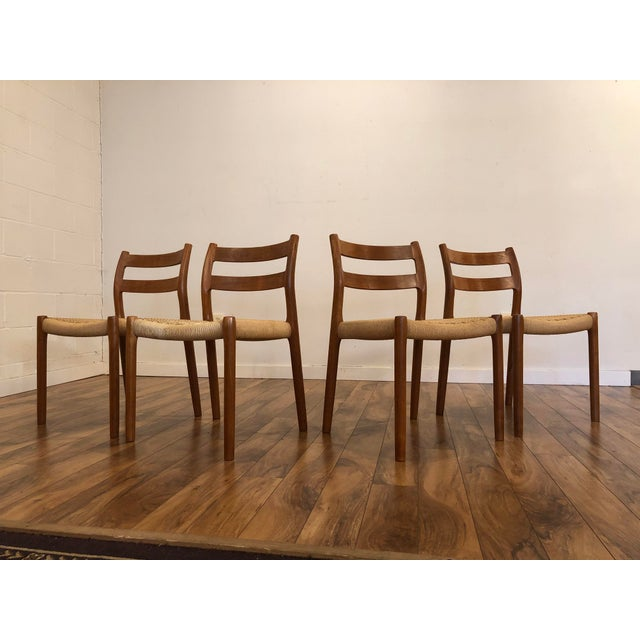 Set of four model No 84 teak dining chairs designed by Niels Otto Moller and manufactured by J.L. Moller. Teak frames are...