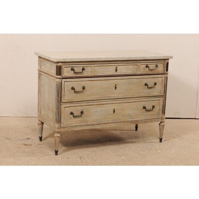 A French early 19th century wood carved chest of drawers with stone top. This antique chest from France features a...