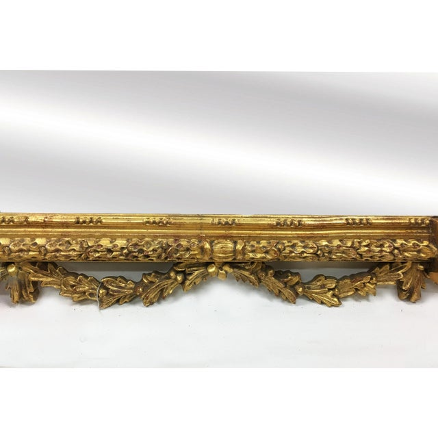 The frame of this large antique mirror is richly carved in the Baroque style and features extensive gilt detail, leaves,...