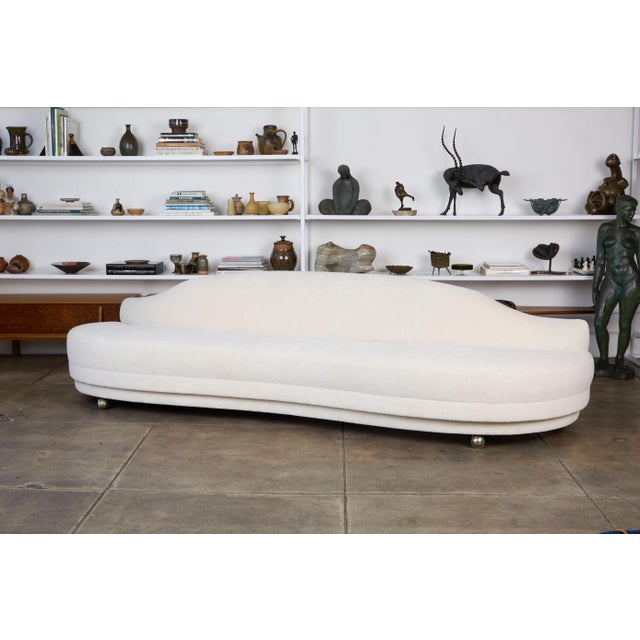 Serpentine alpaca sofa, Los Angeles, c.1950s. The curved sofa has been reupholstered in a luxurious cream colored Italian...