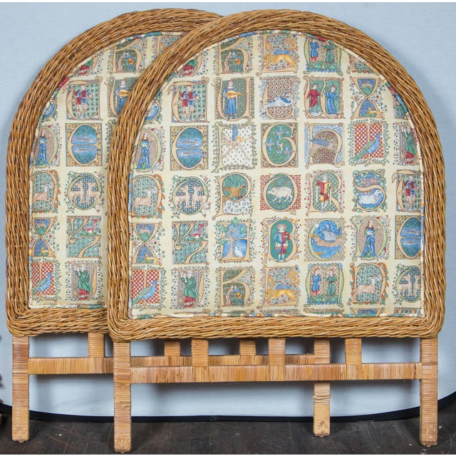 A pair of tall upholstered twin size headboards with thick woven wicker trim and rattan wrapped legs. Upholstery is in...