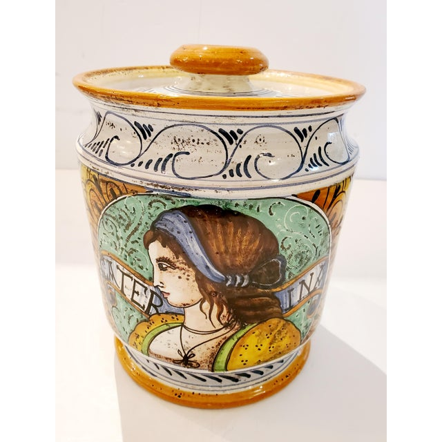 Beautifully painted ceramic lidded jar having a matched male and female with provencal style decoration and color palette.