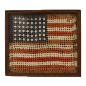American Country (early 20th Cent) folk art embroidery of a US flag portrayed with small pompoms in a wood frame behind glass