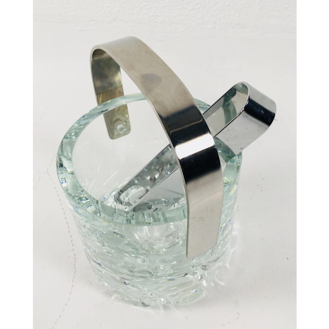 This is an Orrefors Swedish crystal ice bucket complete with nickel plated tongs. New but handsome. Total height of 8...