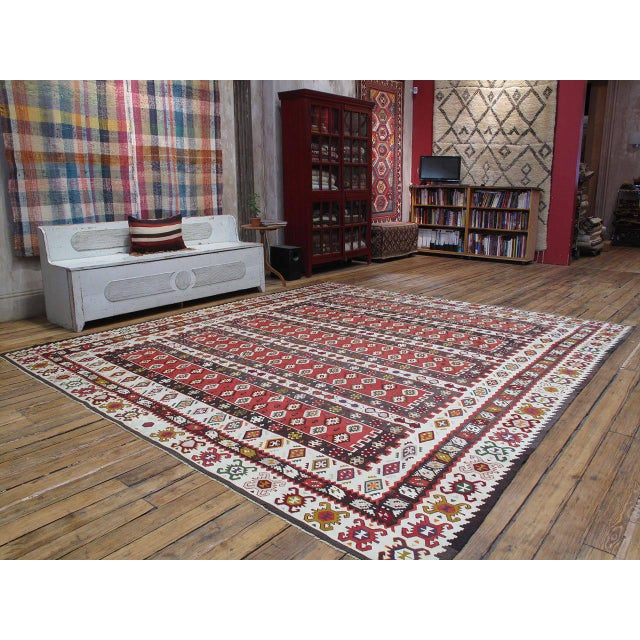 An old flat-woven rug in large, square-ish format from the border region between Serbia and Bulgaria, where the tradition...