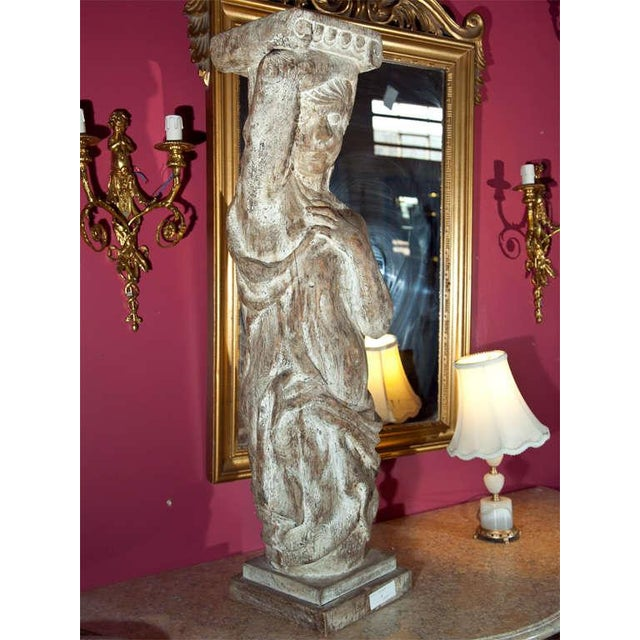 Carved Continental wood figure of a women holding a pillar, supported on a block base.