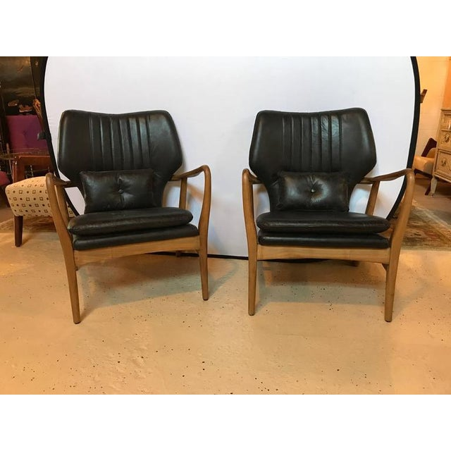 Pair of Danish mid-century modern style leather armchairs. Each on a teak frame with sleek and stylish design. Seat height...