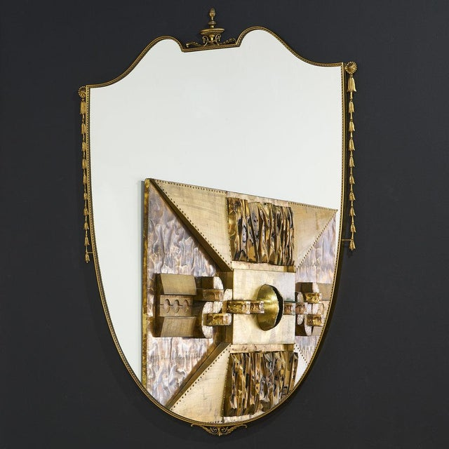 A vintage brass shield mirror with ornamental trim cascading down the side and along the top. Large in scale, this...